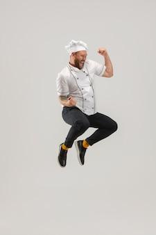 Um homem barbudo, cozinheiro, chef masculino de uniforme branco corta pepino pulando isolado no branco