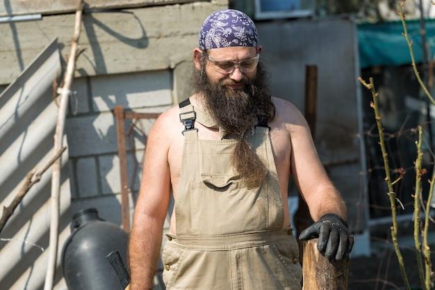 Um homem barbudo de meia-idade com uma bandana corta toras com um machado brutal, de macacão, faz o trabalho difícil