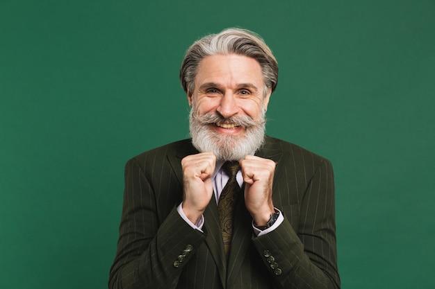 Um homem barbudo de meia-idade, de terno, segura os punhos, dói e se alegra em uma parede verde.