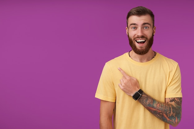 Um homem barbudo de olhos azuis feliz com tatuagens, corte de cabelo curto da moda e camiseta amarela, parecendo alegre com olhos arregalados e boca aberta, isolado no roxo