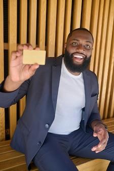 Um homem barbudo, de pele escura e sorridente segurando um cartão de crédito