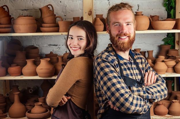 Um homem barbudo e uma jovem estão ao lado da prateleira com vasos e potes de barro. oleiro, argila, vaso, oficina de cerâmica.