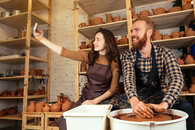 Um homem barbudo e uma jovem moldam um vaso de barro em uma roda de oleiro e fazem uma selfie ao telefone em uma oficina de cerâmica. oleiro, argila, vaso, oficina de cerâmica. mestre e aluno.