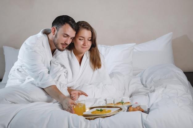Um homem barbudo e uma mulher de jaleco branco estão tomando café da manhã na cama