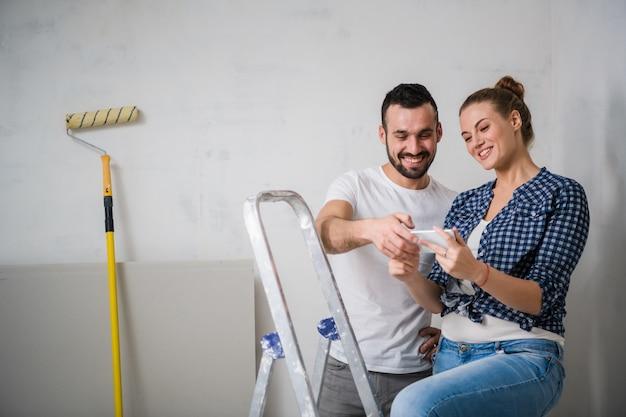 Um homem barbudo e uma mulher olhando uma foto em um smartphone em um apartamento em reforma