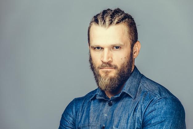 Um homem barbudo em roupas casuais está apontando para fora, sorrindo,