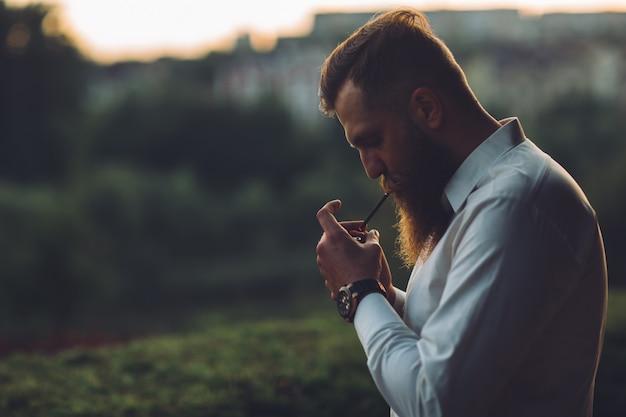 Um homem barbudo está fumando um cigarro contra o pôr do sol.
