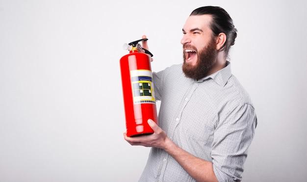 Um homem barbudo está gritando com um extintor de incêndio nas mãos, olhando para longe perto de uma parede branca