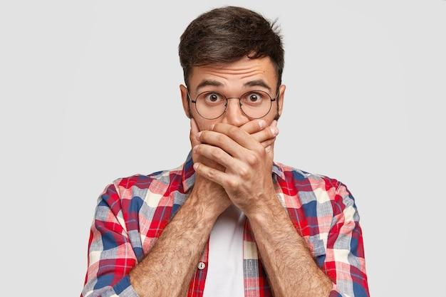 Um homem barbudo fantástico cobre a boca com as duas palmas, sem fala