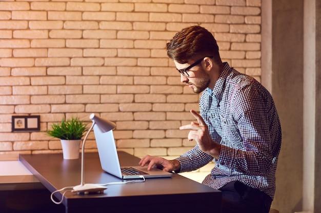 Um homem barbudo freelancer com um laptop funciona