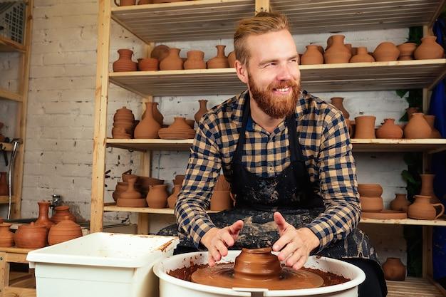 Um homem barbudo moldando um vaso de barro em uma roda de oleiro em uma oficina de cerâmica. oleiro, barro, vaso, cerâmica e oleiro. master e cerâmica ware.