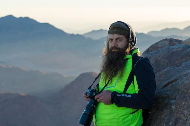 Um homem barbudo na montanha de moisés com uma câmera, peregrinação aos lugares sagrados.