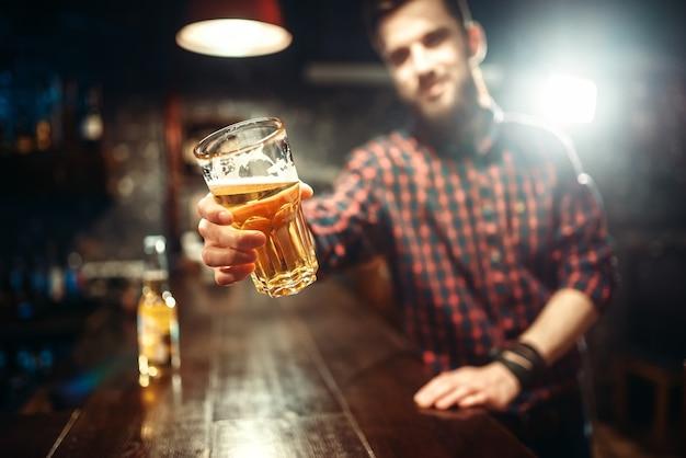 Um homem barbudo segura um copo de cerveja, cara no balcão do bar. lazer masculino em bar
