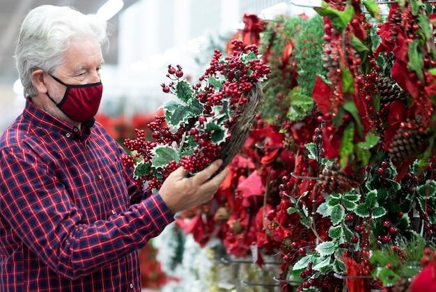 Um homem barbudo sênior com cabelo branco escolhendo uma guirlanda de natal em uma loja para as próximas férias, usando uma máscara vermelha devido ao coronavírus
