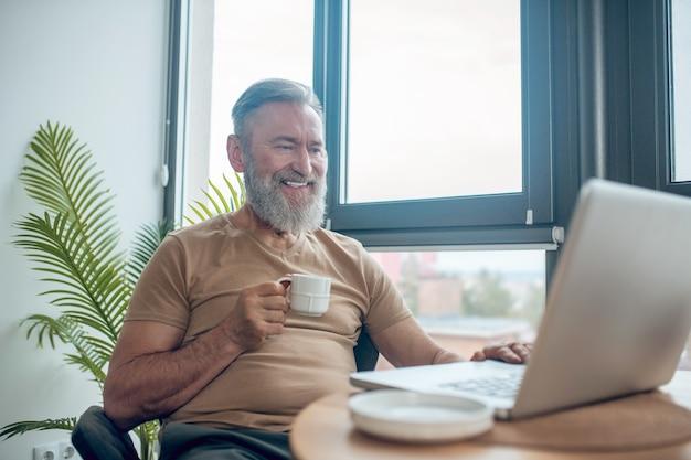 Um homem barbudo sentado em frente ao laptop, conversando com algo online e sorrindo