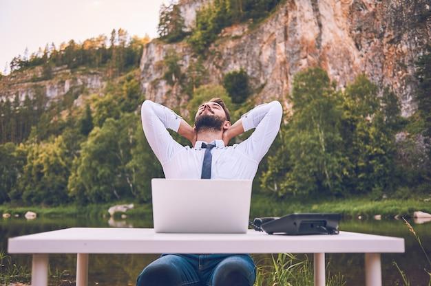Um homem barbudo trabalha com um laptop sobre a natureza. um freelancer feliz está sentado e usando um aplicativo ou site na grama. trabalhe remotamente no modo de auto-isolamento