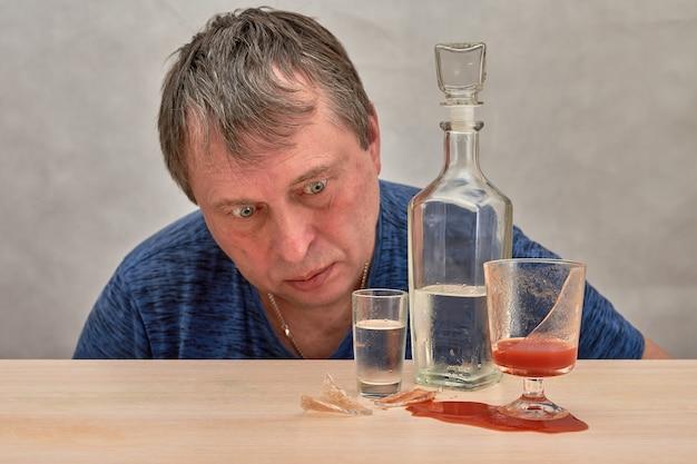 Um homem bêbado olha para o álcool e um copo quebrado de suco de tomate