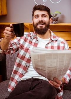 Um homem bebe café e lê um jornal em um café.