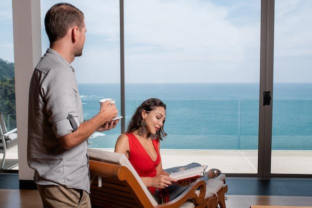 Um homem bebe café e uma mulher lê um livro. um casal está relaxando em uma casa. férias de luxo