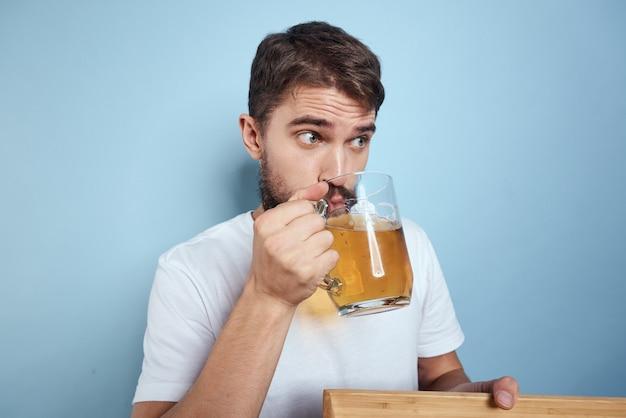 Um homem bebe cerveja de um copo e come fast-food frito