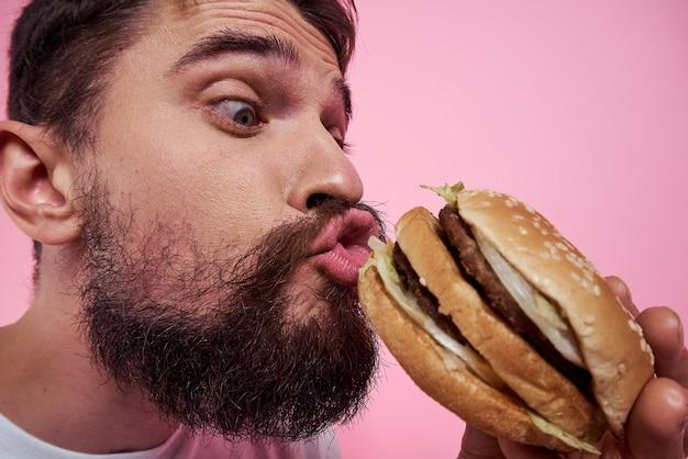 Um homem bebe cerveja em um copo e come fast food frito