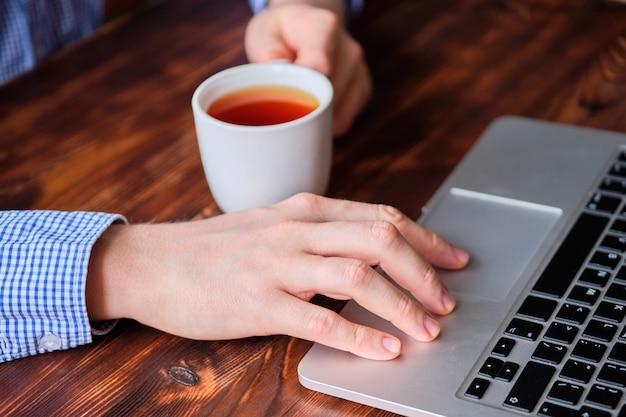 Um homem bebe chá enquanto trabalha atrás de um laptop. o conceito de descanso durante o trabalho.