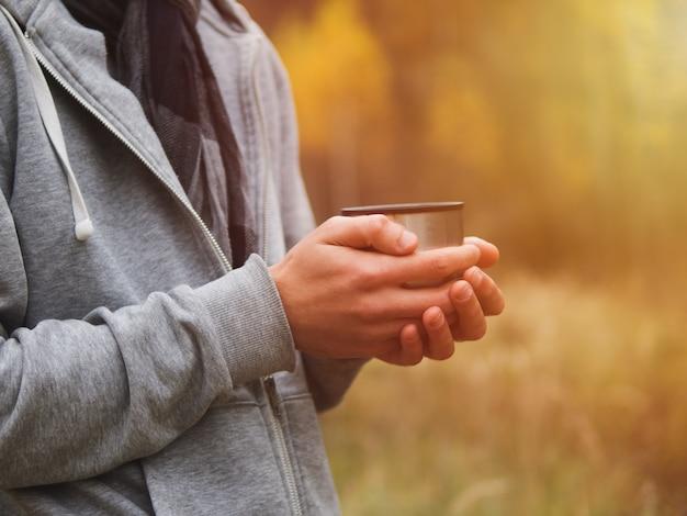 Um homem bebe chá quente de uma garrafa térmica na natureza no outono