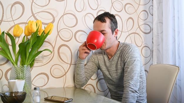 Um homem bebendo chá com flores