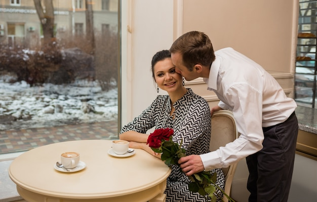 Um homem beija uma linda mulher e dá rosas vermelhas em um café