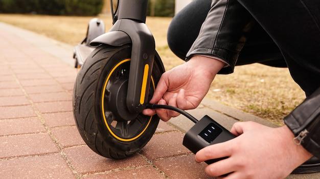 Um homem bombeia ar no volante de uma scooter elétrica usando um dispositivo especial