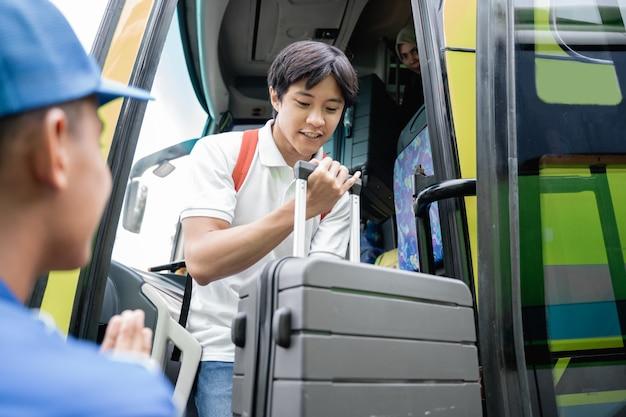 Um homem bonito asiático com mochila e mala saindo de um ônibus de viagem no terminal de ônibus