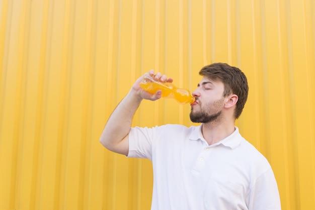Um homem bonito, beber uma bebida de laranja de uma garrafa em uma parede amarela.