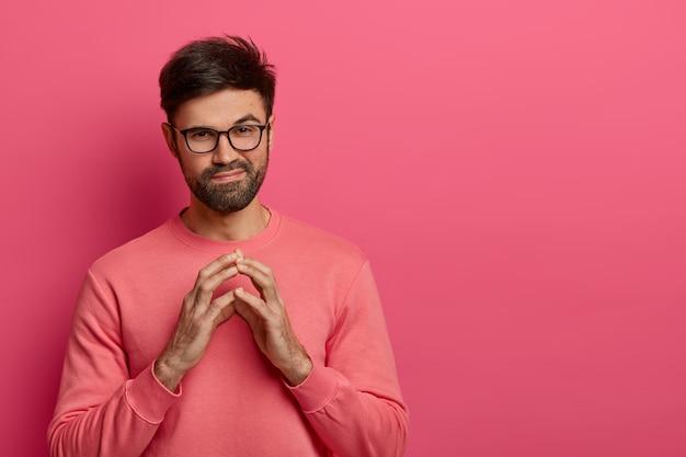 Um homem bonito com a barba por fazer tem um plano maligno complicado, cruza os dedos e parece misteriosamente