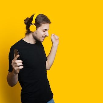 Um homem bonito, com cabelo comprido e barba, está ouvindo música com fones de ouvido enquanto posa perto de amarelo