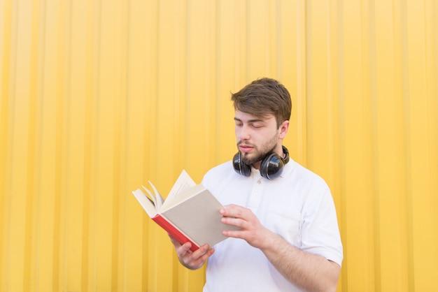 Um homem bonito com fones de ouvido no pescoço está em uma parede amarela e lê um livro.
