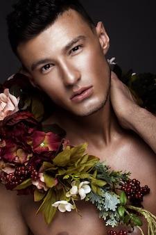 Um homem bonito, com pele bronzeada e flores no corpo.
