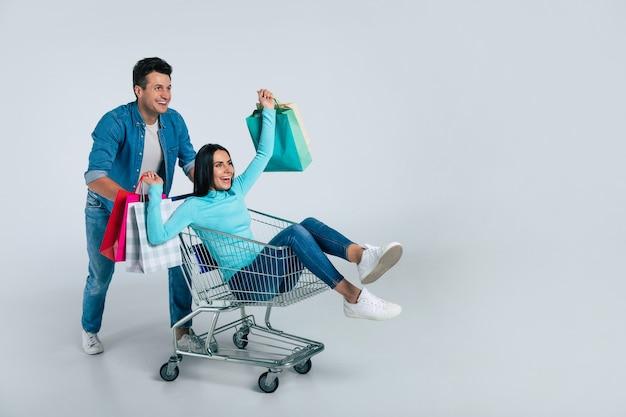 Um homem bonito com roupas do dia a dia está empurrando um carrinho de compras com uma linda garota com sacolas de papel multicolorido nas mãos.