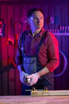 Um homem bonito de meia-idade com óculos de proteção e luvas vai cortar uma peça de metal na garagem