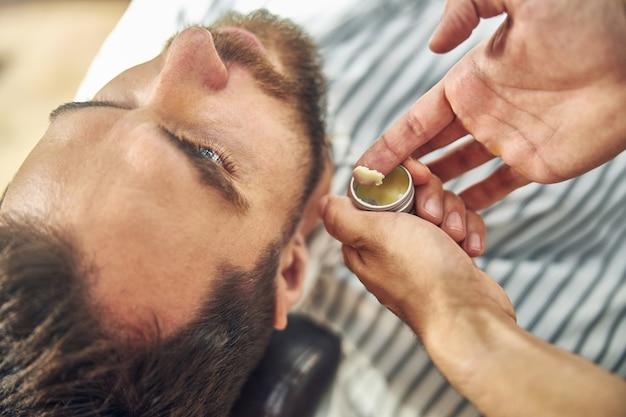 Um homem bonito deitado enquanto seu barbeiro colocava cera de cabelo em seu dedo