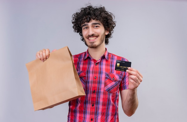 Um homem bonito e feliz com cabelo encaracolado e camisa xadrez mostrando cartão de crédito
