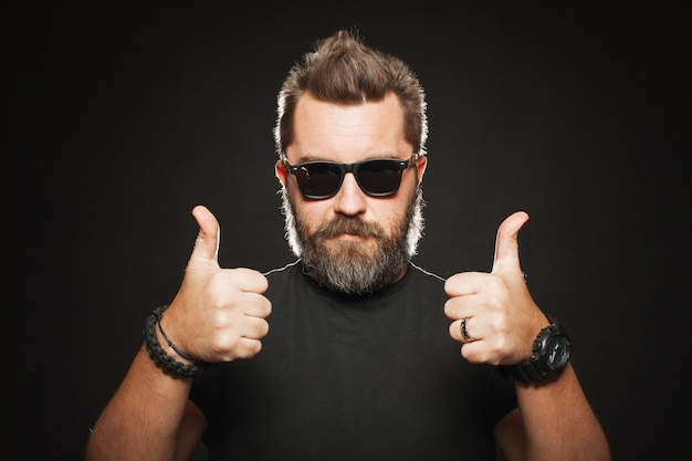 Um homem bonito e forte mostra dois polegares para cima.