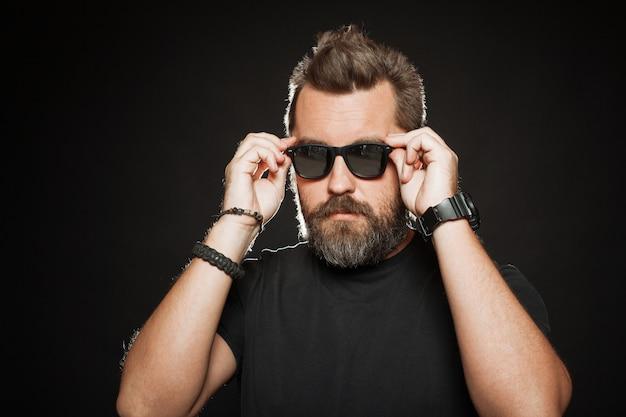 Um homem bonito e forte veste óculos escuros.