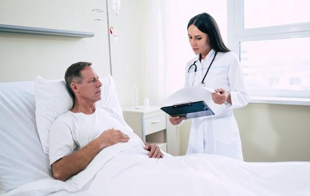 Um homem bonito e maduro está deitado na cama da clínica e conversa com uma jovem médica confiante de jaleco branco