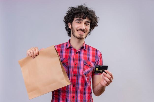Um homem bonito e satisfeito com cabelo encaracolado e camisa xadrez mostrando cartão de crédito