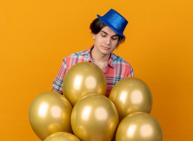 Um homem bonito e satisfeito com um chapéu de festa azul parece e fica de pé com balões de hélio isolados na parede laranja