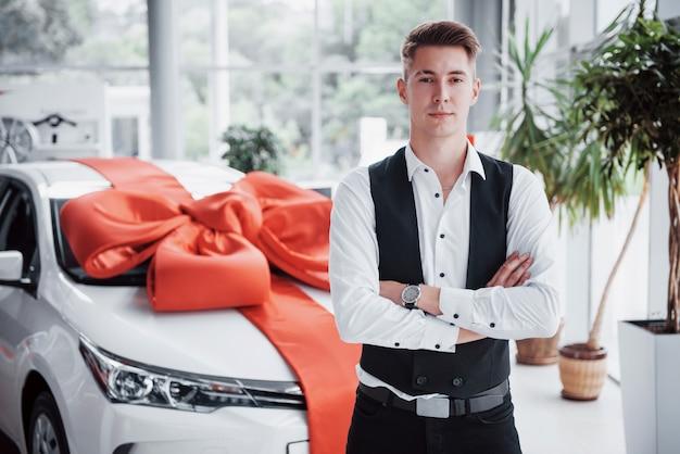 Um homem bonito é um comprador ao lado de um carro novo na concessionária e olhando para a câmera.
