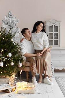 Um homem bonito e uma jovem bonita passam um tempo em casa na véspera de natal