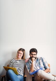 Um homem bonito e uma mulher bonita alegre estão esperando sua entrevista de emprego enquanto estão sentados em cadeiras e segurando pastas no colo.