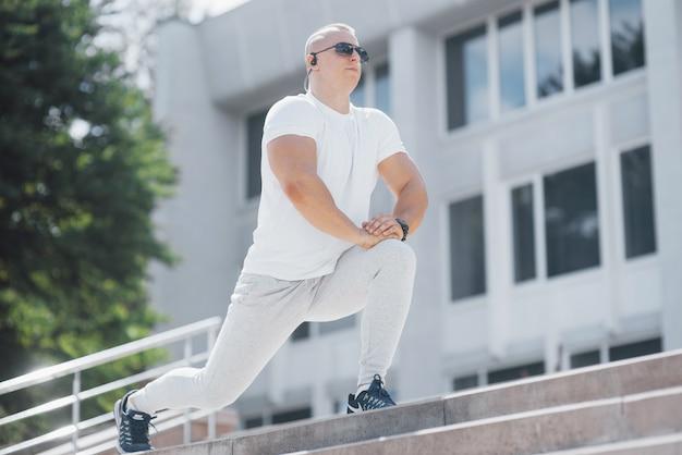 Um homem bonito fitness em um sportswear, fazendo alongamentos enquanto se prepara para exercícios sérios na cidade moderna