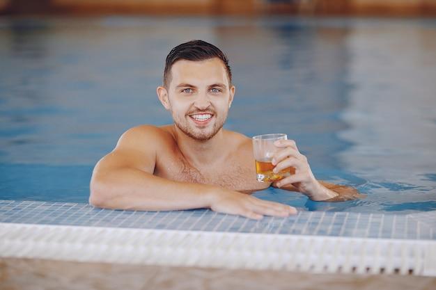 Um homem bonito flutuando em uma grande piscina em casa e bebendo uísque